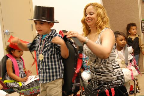 Glenda Robles, a teacher at Easter Seal's All Kids Child Care in Waterbury, helps Steven Torrolli put on his new backpack at the school's End of Year Celebration.