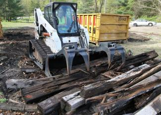 Peter Lipeika, an employee of O&G Industries in Torrington, uses a Bobcat to collect railroad ties at the train depot in East Litchfield on Tuesday. The ties were deposited into Dumpsters that will be hauled away as part of a cleanup effort.